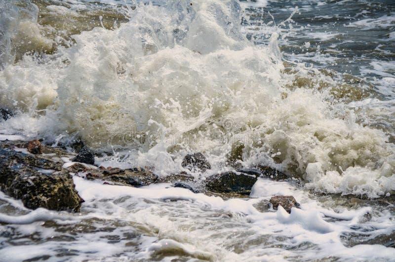 Kraftiga vågor av havet som skummar som bryter mot den steniga kusten royaltyfri foto