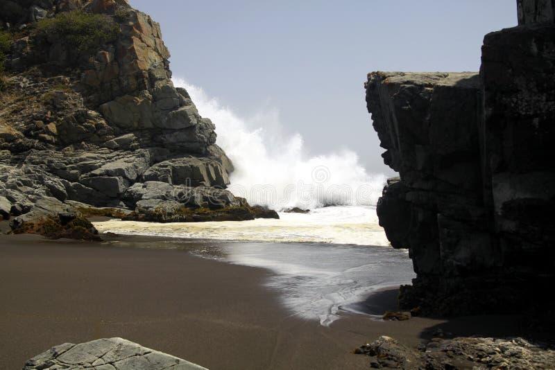 Kraftiga vågor som kraschar på, vaggar och plaskande vatten i luften på den avlägsna svarta lavasandstranden på Stillahavskusten royaltyfri foto