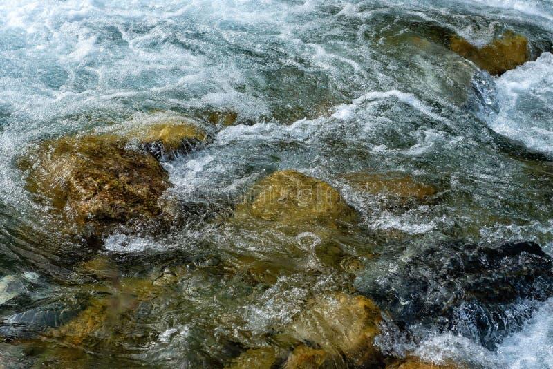 Kraftigt flöde av vatten över stenarna, bergflodslut upp royaltyfri fotografi