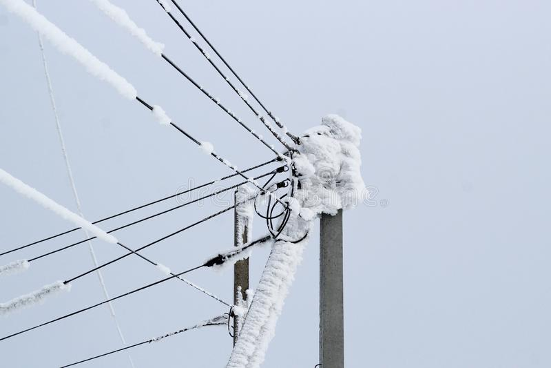 Kraftledning på en pol av många täckte trådar med ett tjockt lager av snö arkivfoton