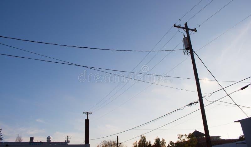 Kraftledningar över en blå himmel arkivfoto