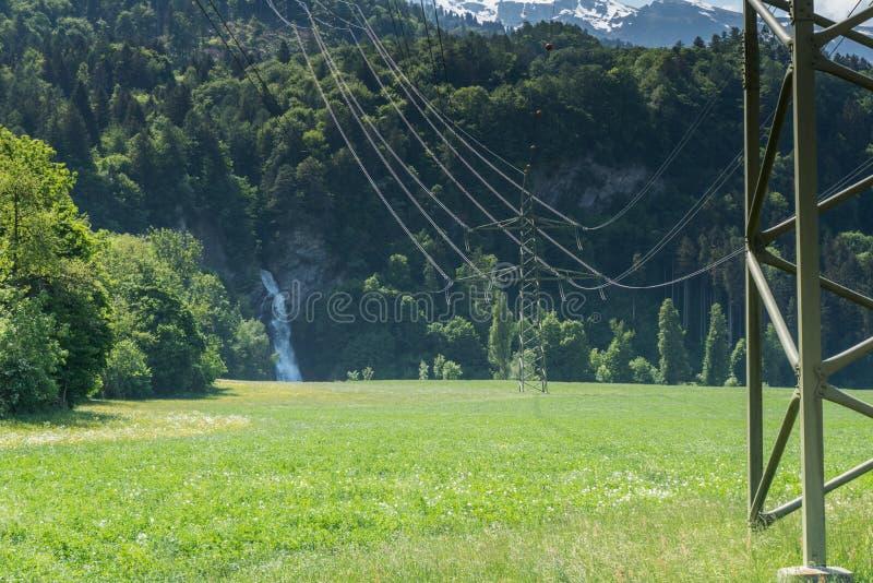 Kraftledningar och elektricitetskablar som leder till ett berg, sid med en vattenfall som symboliserar vattenkraft royaltyfri foto