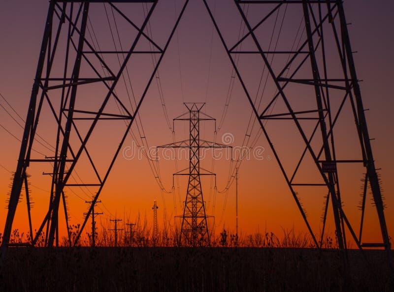 Kraftledningen står högt på soluppgång royaltyfri fotografi