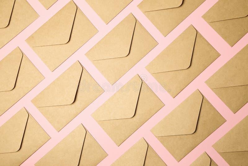 Kraftpapier-document enveloppen op roze achtergrond stock foto's