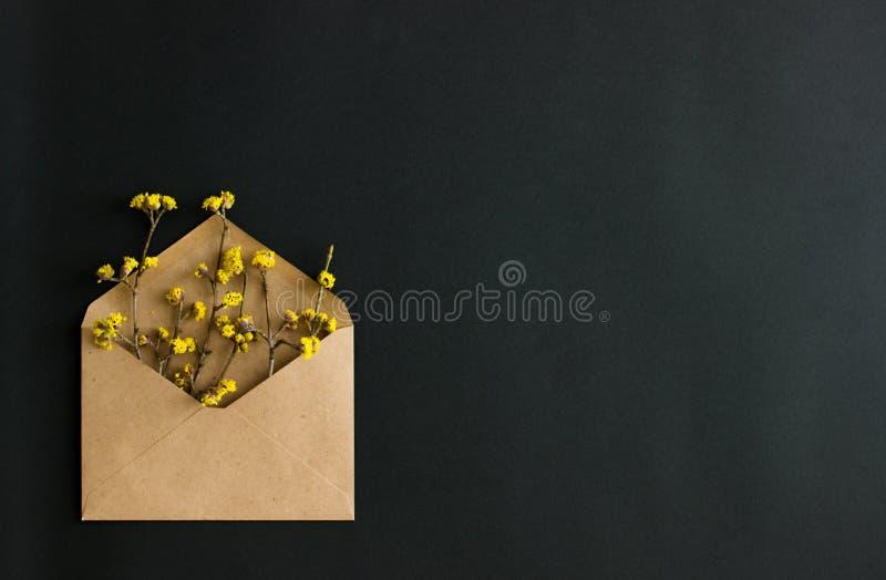 Kraftpapier-envelop met gele bloemen op zwarte achtergrond royalty-vrije stock afbeelding