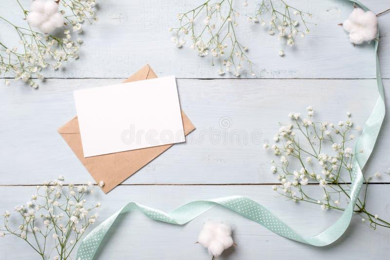 Kraftpapier-envelop met lege kaart voor uitnodiging of gelukwens en bossen van bloemen op lichtblauwe houten achtergrond Wijfje w stock afbeelding
