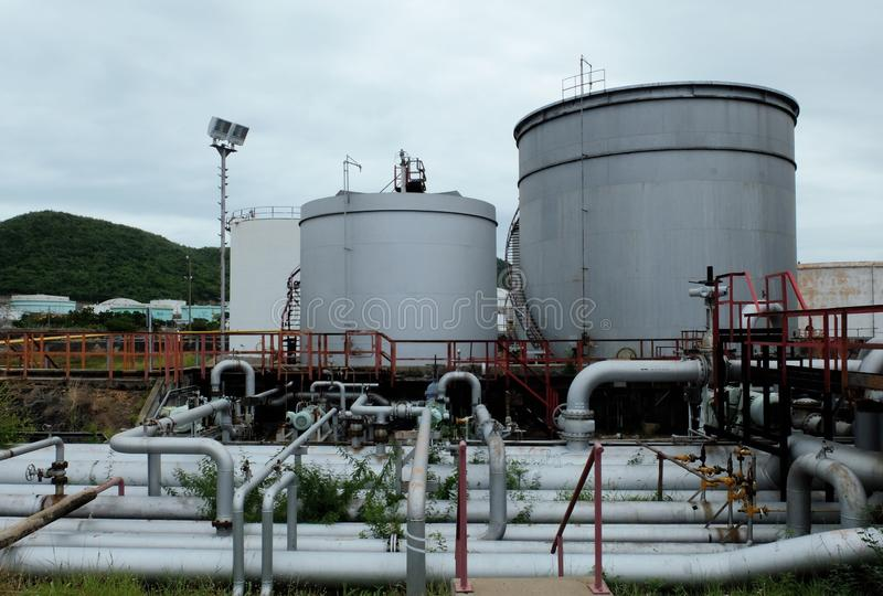 Kraftstofftank mit Rohrleitungen in der Raffinerie an der Dämmerung stockbilder