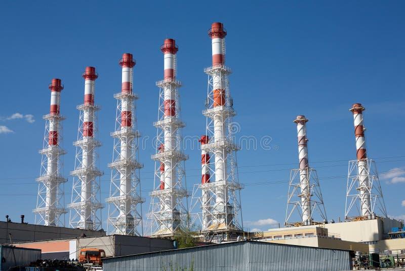 Kraftverkbyggnader med många höga rökrör arkivbilder