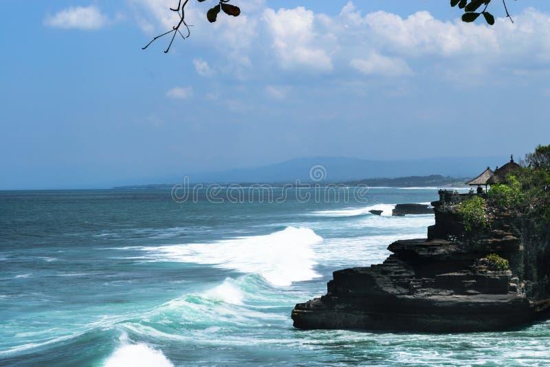Krajobraz Bali wyspy brzeg błękitny ocean indyjski, ogromne fale i czarna faleza z świątynią z zmrokiem -, obraz royalty free