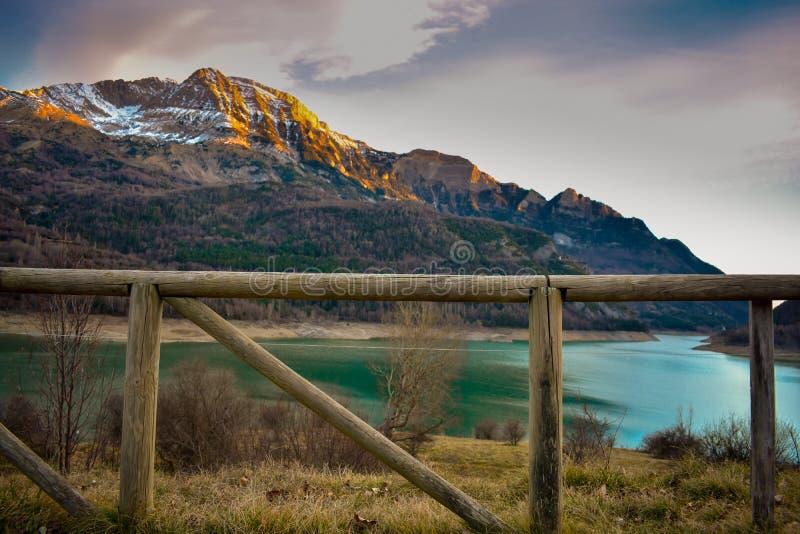 krajobraz drewniany ogrodzenie najpierw strzelał i śnieg na szczytach góry i błękitne wody jezioro w popołudniu obraz stock
