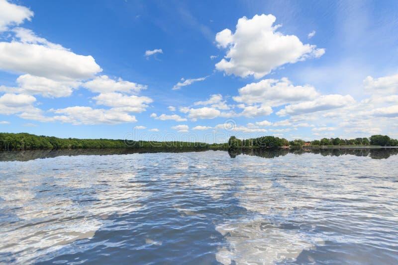 Krajobraz, niebieskie niebo, chmury i wodny odbicie, obraz royalty free