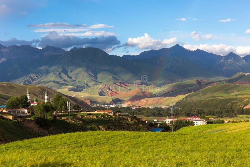 Krajobraz po tym jak deszcz, tęcza, góry, wioski, kościół i paśniki, zdjęcie stock