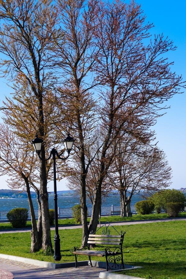 krajobraz w miasto Parkowej ławce pod lampą w jeziorze zdjęcia royalty free