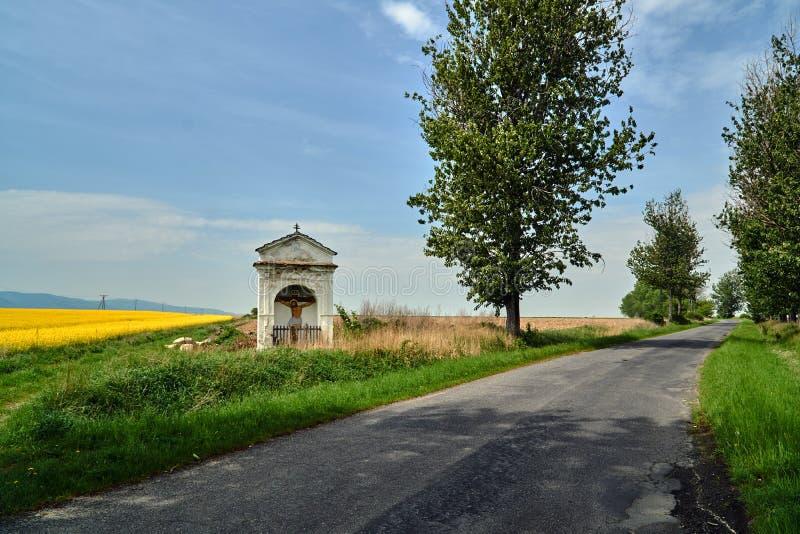 Krajobraz wiejski z przydrożną kaplicą i kwitnącym rzepakiem zdjęcie royalty free