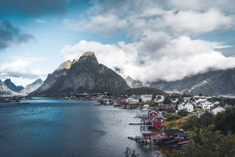 Krajobraz wioska rybacka Reine z Reine Fjord podczas zmierzchu z ładnymi światłami na górze, niebieskim niebie i chmurach, obrazy stock