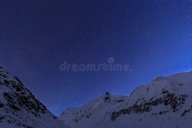 Krajobraz z górami i niebieskim niebem w zimy nocy fotografia stock