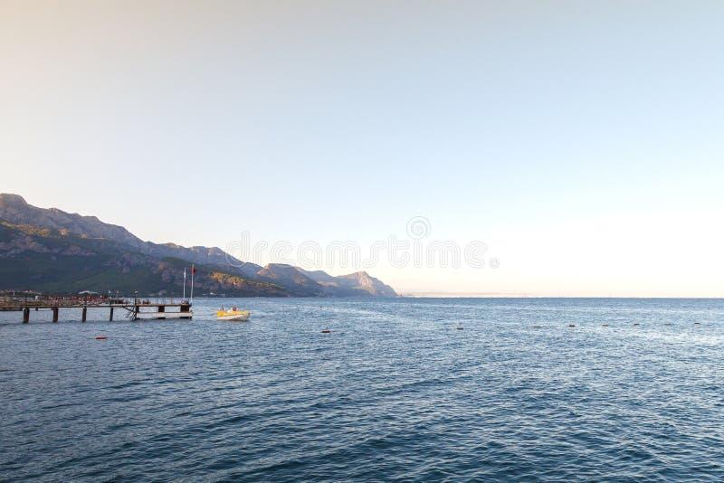 Krajobraz z morzem i łodzią łódkowaty pobliski molo Wieczór, zmierzchu światło słoneczne obrazy stock