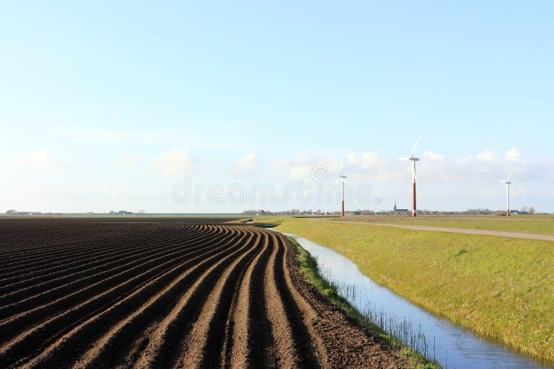 Krajobraz z zmrok orzącymi silnikami wiatrowymi i polem obraz stock