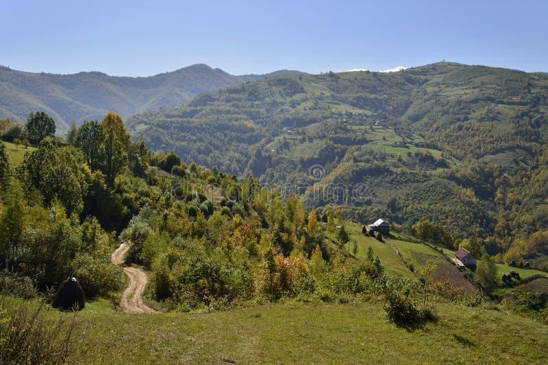 Krajobrazowa wiejska droga i górska wioska na początku jesieni zdjęcie stock