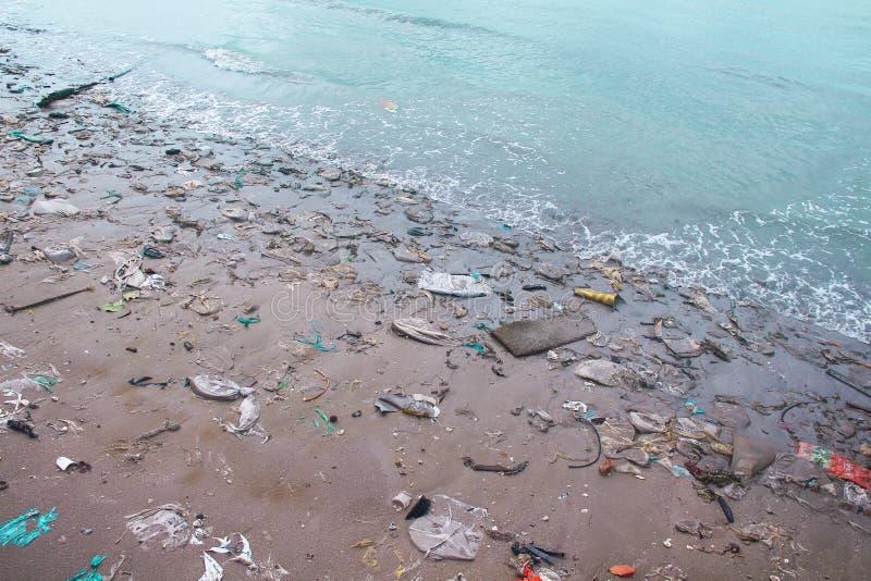 Krajobrazowy denny wybrzeże po burzy, piasek plaża z plastikowym śmieciarskim zanieczyszczeniem fotografia royalty free