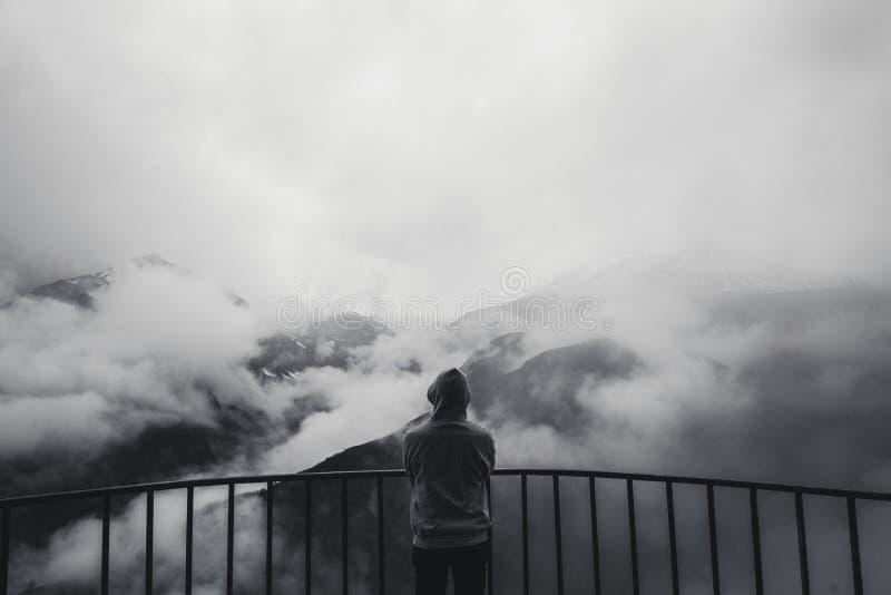 Krajobrazowy widok mglistej jesieni halni wzgórza zakrywający z mgły i mężczyzna sylwetką w kapiszonie Monochromatyczna fotografi obraz royalty free