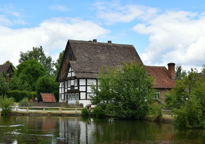 Kraju krajobraz Stary dom na banku spokojna rzeka obraz stock