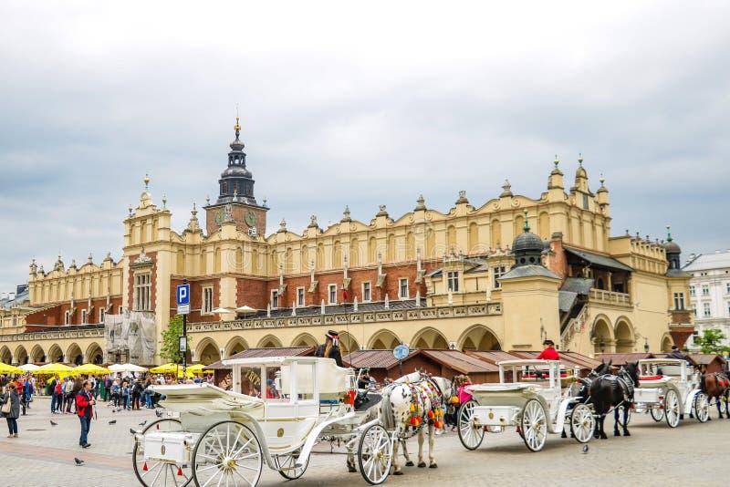 Kraków, Polonia - 21 de mayo de 2019: Carros del caballo en la plaza principal en Kraków foto de archivo libre de regalías