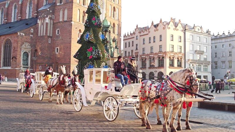 KRAKÓW, POLONIA - ENERO, 14, 2017 carros traídos por caballo retros y la Navidad adornaron la calle vieja turística de la ciudad foto de archivo