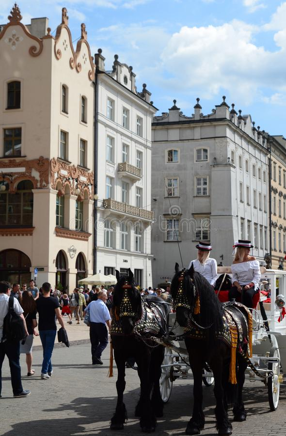 Touristic horse-drawn carriages in the main market square. Krakow. Poland. Kraków is the second largest and one of the oldest cities in Poland, situated on stock photo