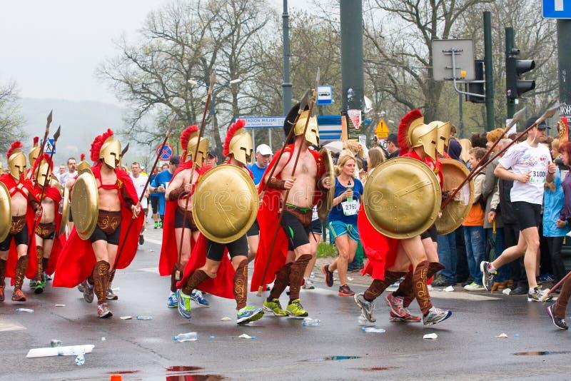 KRAKAU, POLEN - 28. APRIL: Cracovia-Marathon. Spartans-Kindernächstenliebe-Gruppengeschwindigkeit auf den Stadtstraßen lizenzfreie stockfotos
