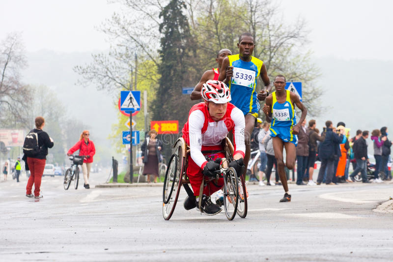 KRAKAU, POLEN - 28. APRIL: Mann-Marathonläufer Cracovia Marathon.Handicapped in einem Rollstuhl auf den Stadtstraßen lizenzfreie stockfotos