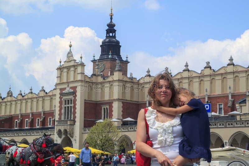 Krakau, Polen - 11 juni 2018: Mooie meid met vermoeide dochter op het plein van Krakau concept reizen met kinderen stock fotografie