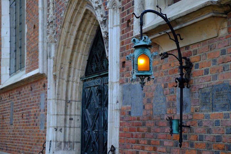 Krakau, Polen - Maart 30, 2018: Lichtgevende lamp op de de bouwmuur Bazylika Mariacka stock afbeeldingen