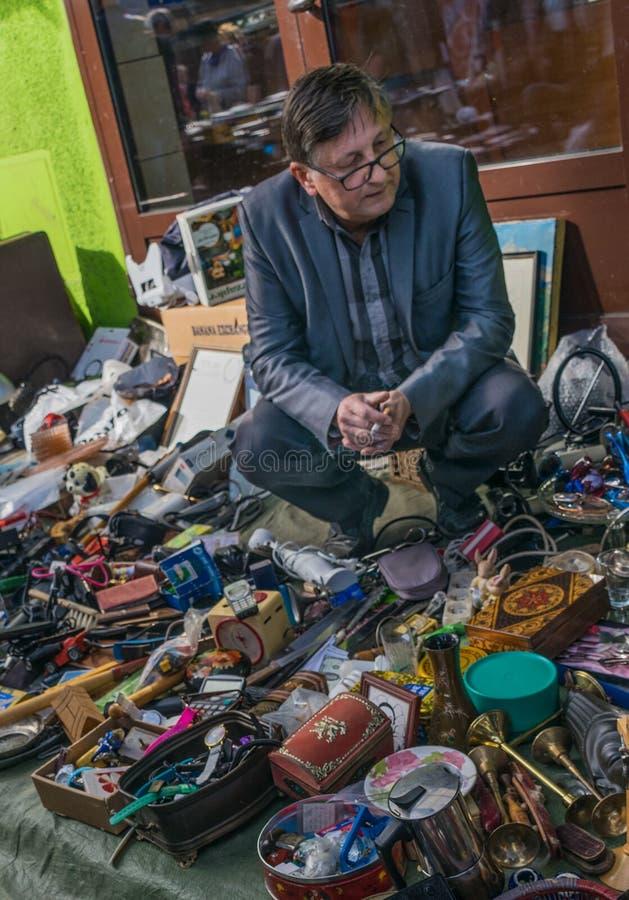 Krakau, Polen - September 21, 2018: Goed geklede poetsmiddelverkoper die op kopers wachten Hij verkoopt gebruikte vervangstukken  stock fotografie