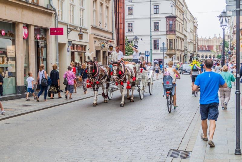 KRAKAU, POLEN - 3. SEPTEMBER 2016: Pferdewagen mit Touristen überschreitet durch Straßen von Krako stockbilder