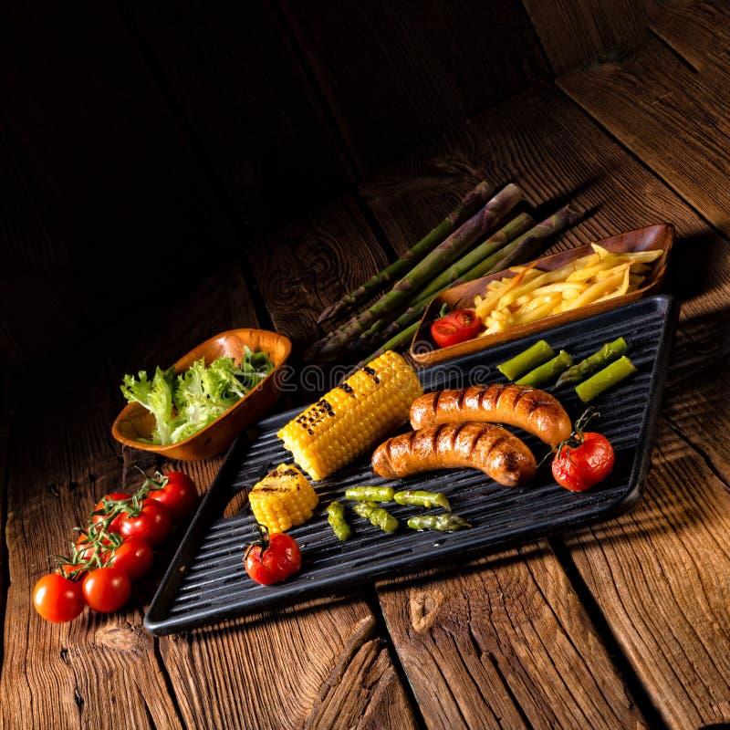 Krakauer grelhado com batatas fritas e salada verde imagem de stock royalty free