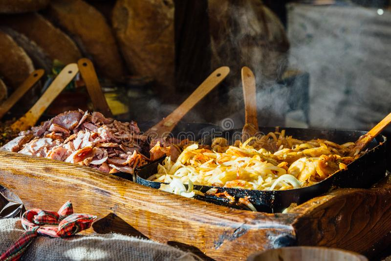 Krakow Christmas market food stall. Krakow Christmas market stall serving traditional slices of bread with grilled meat, onions and sauce stock photography