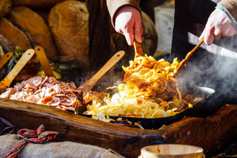 Krakow Christmas market food stall. Krakow Christmas market stall serving traditional slices of bread with grilled meat, onions and sauce stock photo