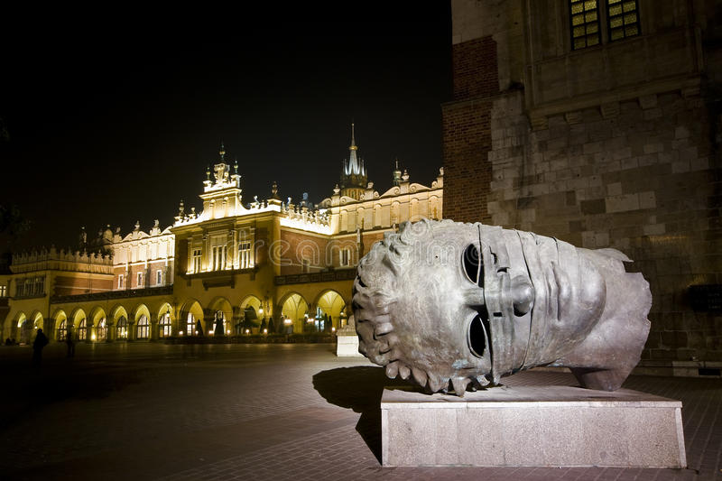 Krakow main square at night. With a sculpture in foreground royalty free stock image