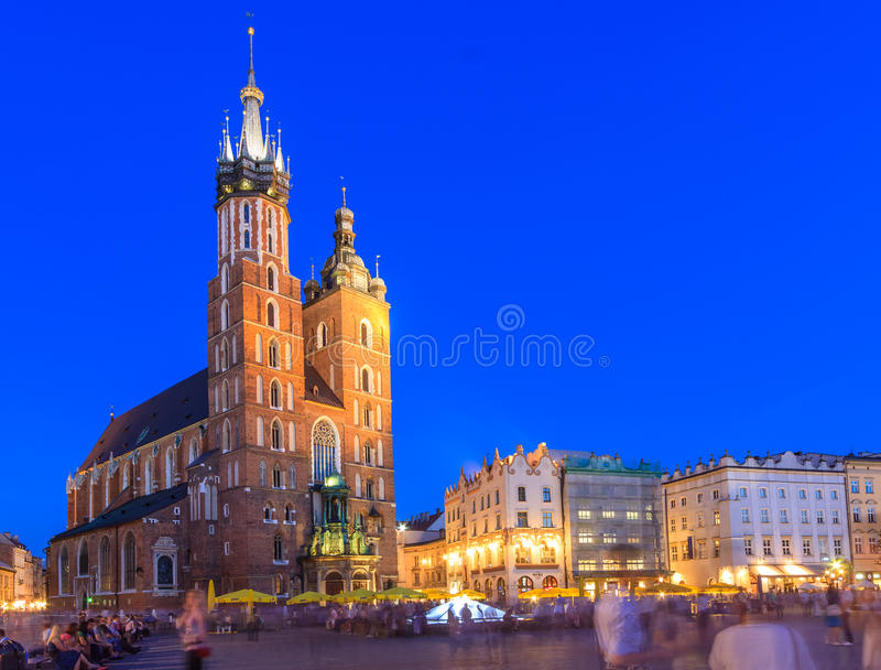 Krakow main square. KRAKOW, POLAND - APRIL 28th 2012: People walking on the Krakow main square with the st. Mary church in the background in the early evening stock photos