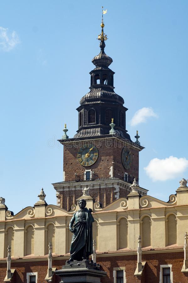 Krakow market square. Detail of the statue and in the background the clock tower, UNESCO World Heritage site royalty free stock images