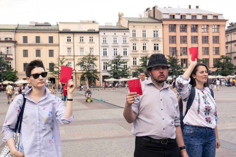 Krakow, Polônia, o 1º de junho de 2018, três povos com os cartões vermelhos no th imagem de stock royalty free