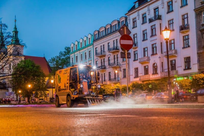 krakow poland April 25, 2019 Den speciala renhållningmaskinen tvättar gatan Aftonlokalvård arkivfoton