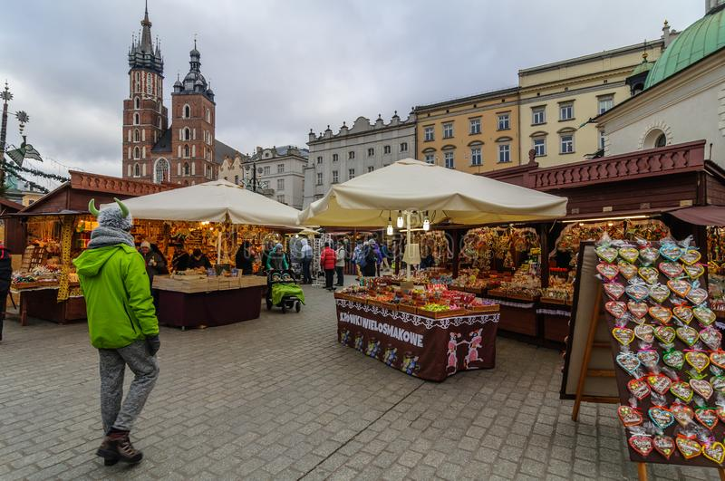 KRAKOW, POLAND - DEC. 29, 2016: Christmas fair in the Market Square along the Krakow Cloth Hall near the town hall. In cloudy weather royalty free stock image