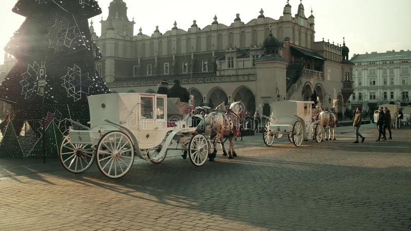 KRAKOW, POLAND - JANUARY, 14, 2017 Horse drawn carriages and Christmas decorated Old town street. KRAKOW, POLAND - JANUARY, 14, 2017 Horse drawn carriages and stock image