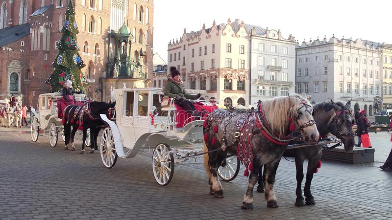 KRAKOW, POLAND - JANUARY, 14, 2017 Horse drawn carriages and Christmas decorated touristic Old town street on a sunny. KRAKOW, POLAND - JANUARY, 14, 2017 Horse royalty free stock photo
