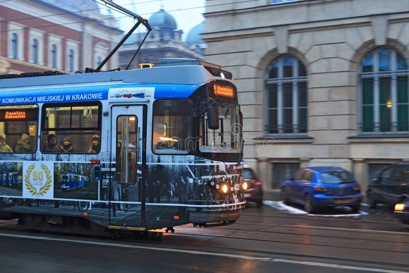 KRAKOW, POLAND - JANUARY 06, 2016: Modern public tram in motion on the street road in historical center of Krakow stock image