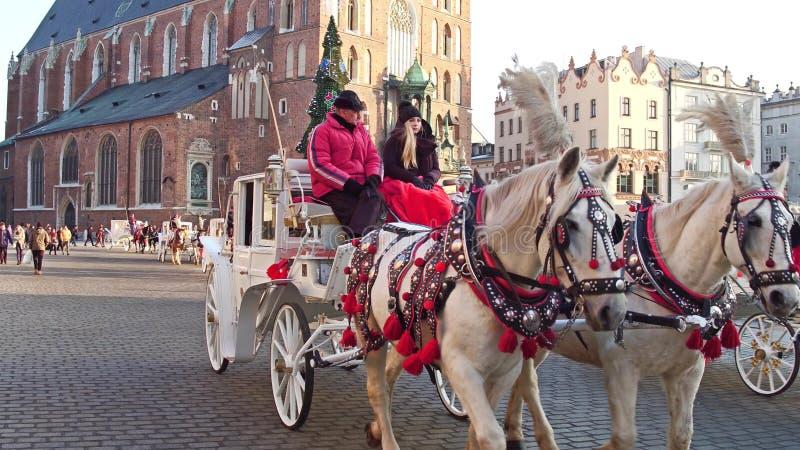 KRAKOW, POLAND - JANUARY, 14, 2017 Retro horse drawn carriage and Christmas decorated touristic street. KRAKOW, POLAND - JANUARY, 14, 2017 Retro horse drawn stock images
