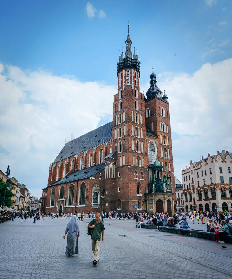 KRAKOW, POLAND - JUNE 28, 2016: People walk in front of St. Mary Church (Mariacki Church) on main market square on nice summer stock photography