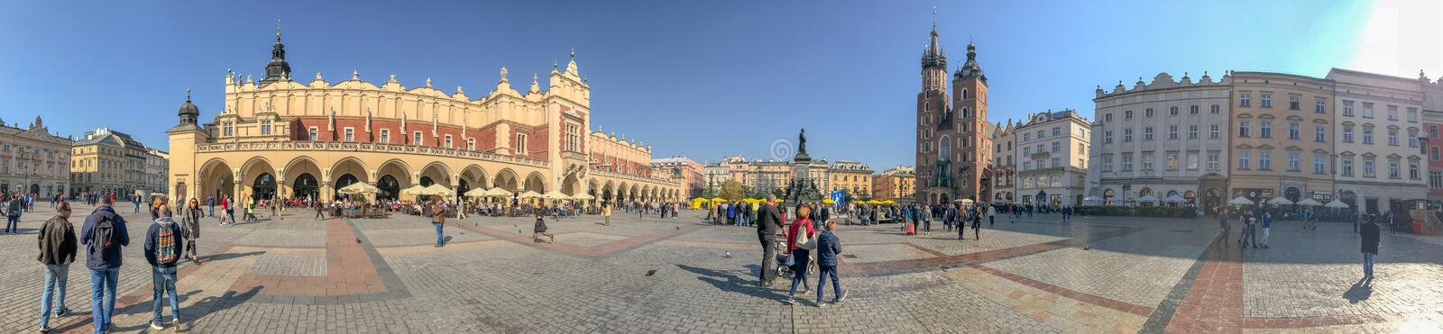 KRAKOW, POLAND - OCTOBER 2, 2017: Tourists visit main square, pa. Noramic view. The city attracts 3 million visitors annually royalty free stock image
